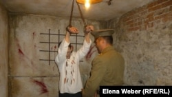«Камера пыток» в музее политических репрессий в поселке Долинка. Подвешенного узника Карлага, которого изображает работник музея, пытает импровизированный сотрудник НКВД. Карагандинская область, 18 мая 2013 года.