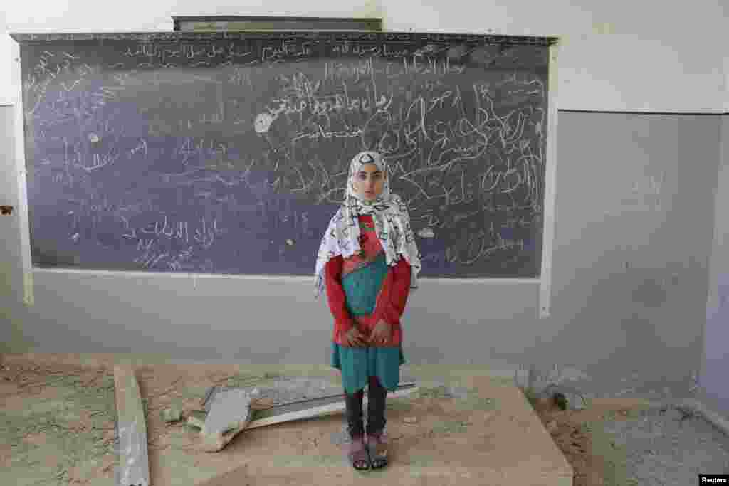 Malak, a 13-year-old girl, poses for a picture inside her damaged classroom at a school used as a military camp for forces loyal to Syria's President Bashar al-Assad, in the rebel-controlled town of Ain Qurei. (Reuters/Khalil Ashawi)