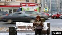 Пожилая женщина на скамейке в центре Москвы.