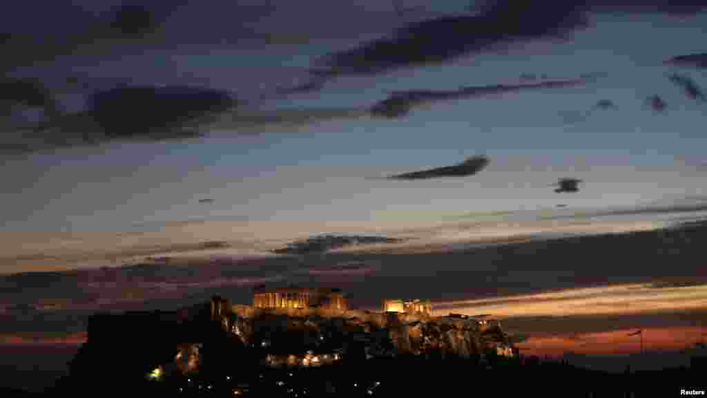 The temple of the Parthenon is illuminated at the Acropolis hill in Athens. (Reuters/John Kolesidis)