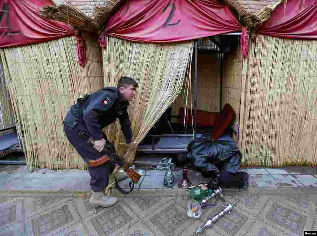Police officers search for shisha water pipes inside a cafe during a raid in Kabul, Afghanistan. (Reuters/Mohammad Ismail)