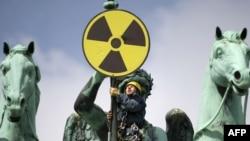 یکی از فعالان صلح سبز آلمان در حالی که علامت مخالفت با انرژی اتمی را در دست دارد- برلین
