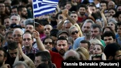 """A protester sports the word """"no"""" in Greek on his forehead as he waves a Greek flag during an antiausterity demonstration in Syntagma Square in Athens on July 3."""