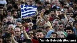 Греческий флаг посреди толпы людей во время демонстрации против мер жесткой экономии. Афины, 3 июля 2015 года.