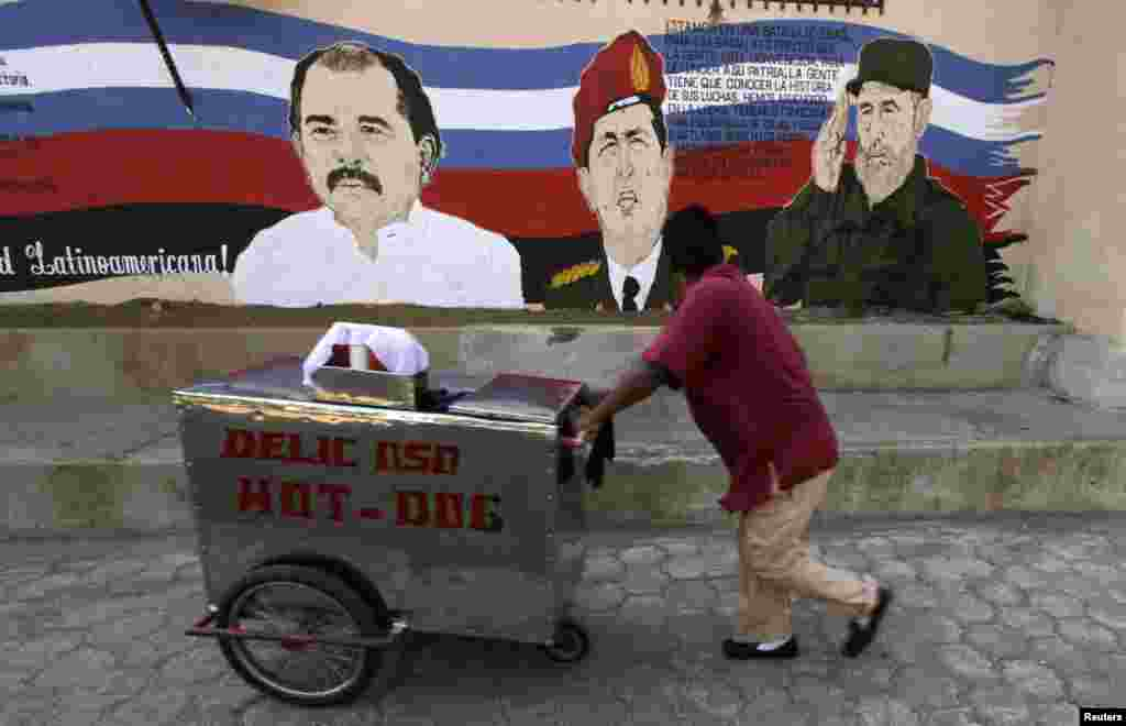 A street vendor in Managua, Nicaragua, pushes his cart past a mural depicting Venezuela's late President Hugo Chavez (center), former Cuban leader Fidel Castro (right), and Nicaraguan President Daniel Ortega. (Reuters/Inti Ocon)