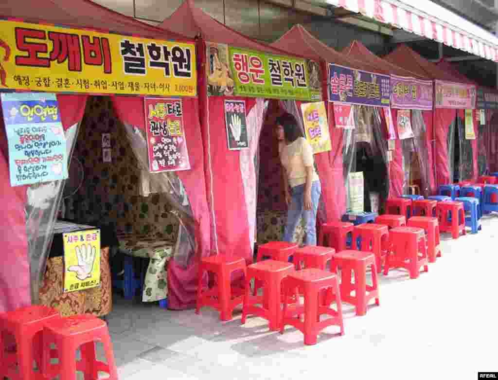 با وجود پيشرفت های چشمگير تکنولوژيک در کره جنوبی، هنوز هم آداب و رسوم ديرين در همه جا قابل مشاهده است. (راسته کف بين ها و فالگيرها در بوسان)