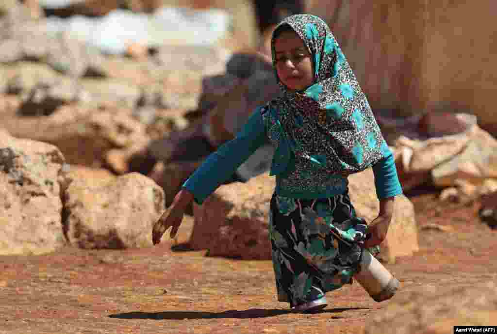 Using prosthetic legs made by her father from tin cans, 8 year-old Maya Mohammad Ali Merhi walks in a camp for displaced people in the northern Syrian province of Idlib. (AFP/Aaref Watad)