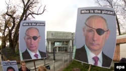 Activists of the environmental organization Robin Wood hold placards depicting Russian President Vladimir Putin as they demonstrate in front of the International Tribunal for the Law of the Sea.