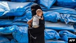 Женщина с младенцем в лагере беженцев, Сирия, иллюстративное фото
