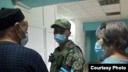 Осужденный активист Кенжебек Абишев в коридоре больницы в сопровождении конвойного рядом со своим адвокатом Гульнарой Жуаспаевой. Капшагай, 15 апреля 2021 года.
