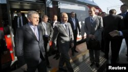Russian President Vladimir Putin (center) and International Olympic Committee (IOC) President Thomas Bach (left front) exit a commuter train at a newly built railway station in Sochi on October 28.