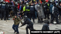 Donald Trump amerikai elnök támogatói összecsapnak a rendőrökkel és a biztonsági erőkkel, miközben megrohamozzák a Capitolium épületét Washingtonban, 2021. január 6-án