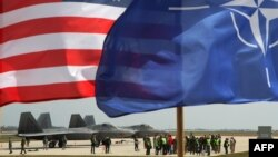 The U.S. and NATO flags fly in front of two U.S. Air Force F-22 Raptor fighter jets at the air base in Siauliai, Lithuania, on April 27.