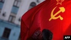 Simferopolun Lenin meydanında kişi SSRİ bayrağını öpür