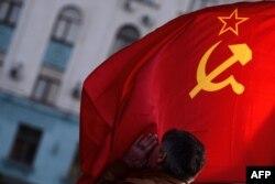 Мужчина целует советский флаг в центре города Симферополь. 16 марта 2014 года.
