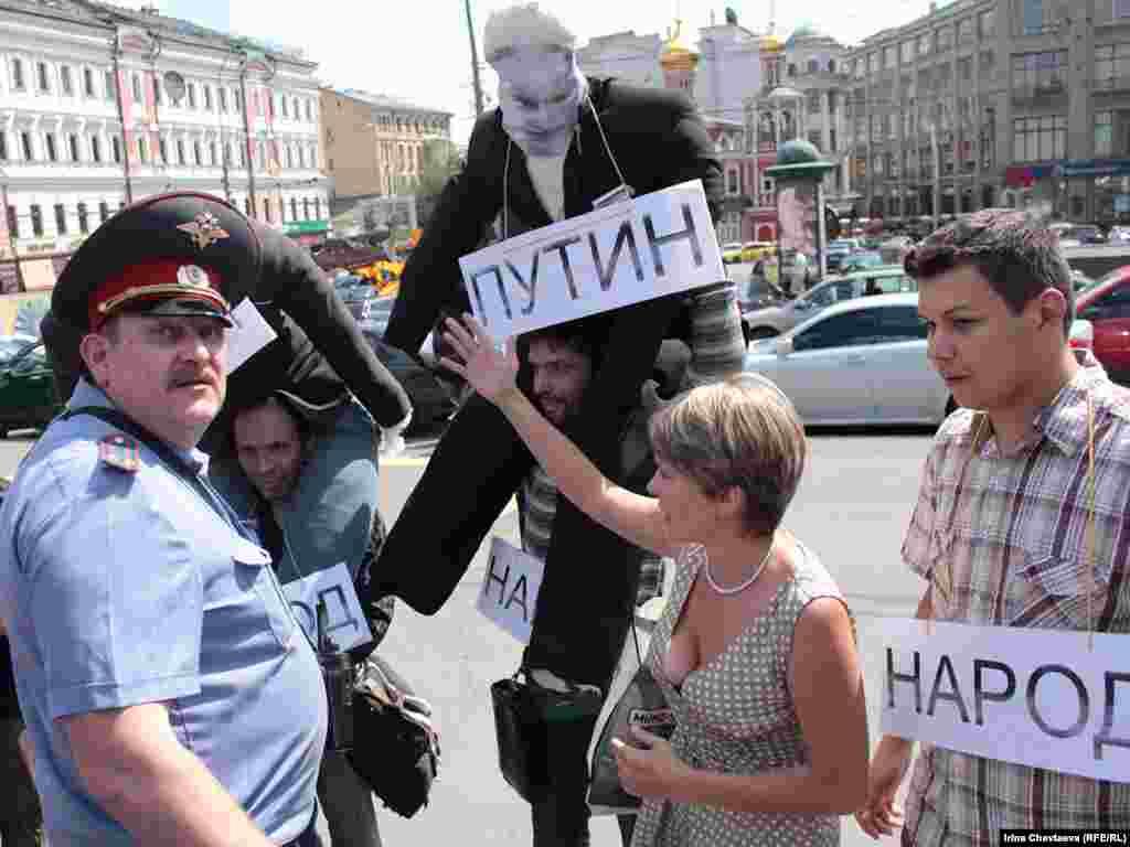 Они появились с большими куклами на плечах, изображающих главу Минтранса Игоря Левитина, премьер-министра России Владимира Путина и бизнесмена Аркадия Ротенберга.