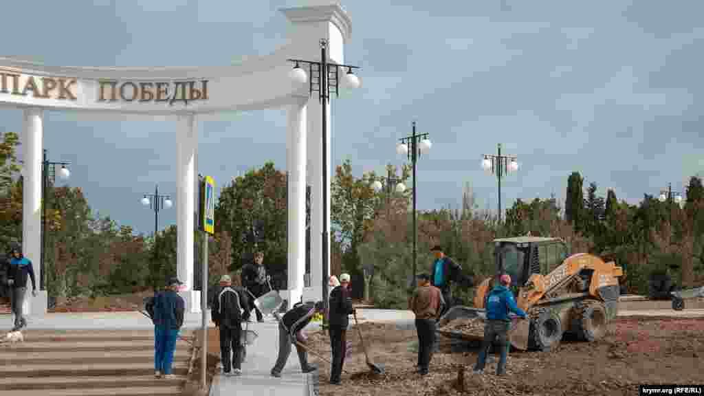 У вход в Парк Победы со стороны проспекта Октябрьской революции идут работы, рабочие выравнивают землю и вывозят строительный мусор