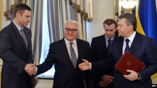 German Foreign Minister Frank-Walter Steinmeier (center) and opposition leader Vitali Klitschko (left) shake hands as Ukrainian President Viktor Yanukovych (right) gestures after signing an agreement in Kyiv on February 21.