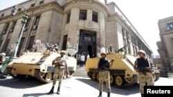 جنود ومصفحات أمام مقر دائرة النائب العام المصري، مع تقدم متظاهرين يطالبون بإطلاق سراح الرئيس المعزول محمد مرسي.