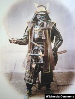 Zirehli geyimini geymiş samuray. 1860-cı illər. Əllə rənglənmiş foto. Britaniya fotoqrafı Felice Beato.
