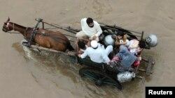 Пәкістандық отбасы су тасқынын болған аймақтан көшіп барады. Лахор, 4 қыркүйек 2014 жыл,.