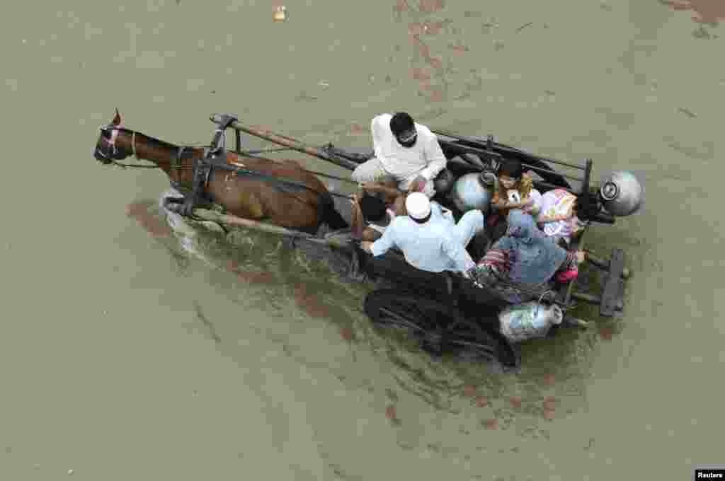 A Pakistani family travels on a horse cart on a flooded road following heavy rain in Lahore. Torrential rain has claimed dozens of lives. (Reuters/Mohsin Raza)