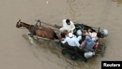 Një familje pakistaneze duke u larguar nga territori i përfshirë nga vërshimet në Pakistan