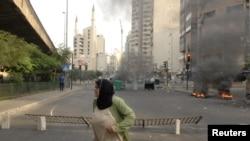 Բեյրութցի կինը փորձում է ապաստան գտնել լիբանանյան բանակի եւ սուննի մահմեդականների բախման ժամանակ, 22-ը հոկեմբերի, 2012