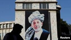 Adamlar prezident Hamid Karzaýyň köçedäki porteriniň deňindan geçip barýarlar. Kabul, 26-njy iýun, 2014.