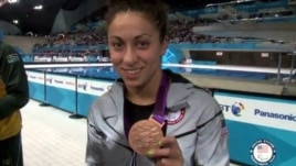 Elizabeth Stone shows one of her bronze medals during the victory ceremony in London in August.