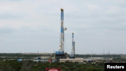 Rigs contracted by Apache Corp drill for crude oil locked tight in shale in west Texas' Permian Basin near the town of Mertzon, Texas, October 29, 2013