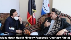 Hakeem Alakozai (R) talks with a an Afghan health ministry official in Kabul on May 30.