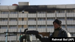 An Afghan police officer stands guard in front of the Intercontinental Hotel in Kabul on January 23.