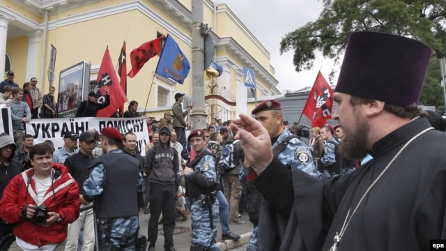 An Orthodox priest blesses demonstrators protesting against Patriarch Kirill's visit to Ukraine.