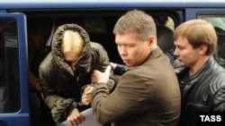 Altyn Deputy Chairwoman Anatonina Babosyuk hides her face as she is escorted to Moscow's Lefortovo court on October 9.