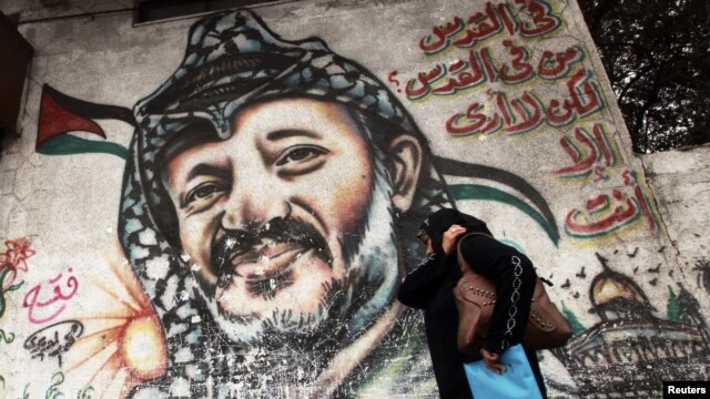 A woman walks past a mural depicting the late Palestinian leader Yasser Arafat in Gaza City.