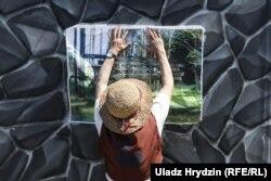 Ніна Багінская вешае фота крыжоў на плот рэстарацыі каля Курапатаў