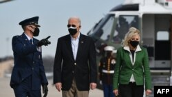 "U.S. President Joe Biden, seen with First Lady Jill Biden, says the U.S. air strike in Syria was a warning that ""you can't act with impunity."""