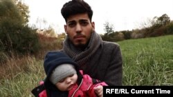Беженец Махмед Али с ребенком