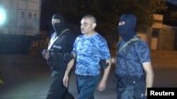 Сотрудники сил безопасности Армении ведут мужчину, который вместе с группой вооруженных людей удерживал здание полиции в Ереване. 31 июля 2016 года.
