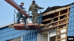 Робітники ремонтують пошкоджену частину даху будівлі польського консульства в Луцьку, 29 березня 2017 року