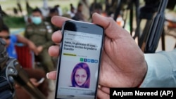 A local journalist shows a story published by an Italian news site regarding Sana Cheema, an Italian woman of Pakistani origin, in the neighborhood of Mangowal, near Gujrat.
