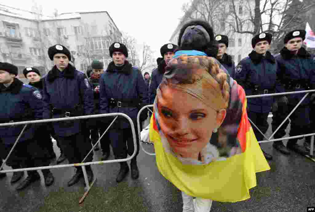 An activist wears a banner with a portrait of Yulia Tymoshenko as she attends a protest rally in front of President Viktor Yanukovych's offices in Kyiv. (AFP/Sergei Supinsky)