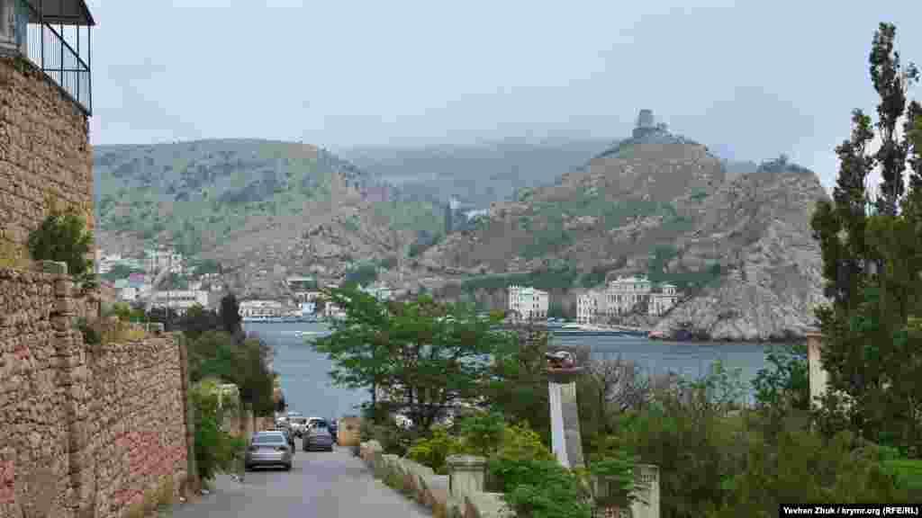 Дорога на пляж «Васили» начинается с находящейся на западном берегу Балаклавской бухты Таврической набережной. На противоположной стороне видны развалины генуэзской крепости Чембало