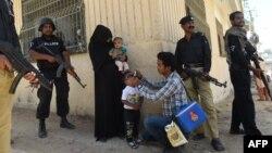 Карачи. Полицейские охраняют сотрудника службы здравоохранения, делающего прививку от полиомеилита ребенку, на следующий день после того, как было совершено нападение на медработника