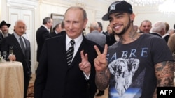 Russian Prime Minister Vladimir Putin (left) poses for a photo with rapper Timati during a meeting with his campaign activists in Moscow in March 2012.