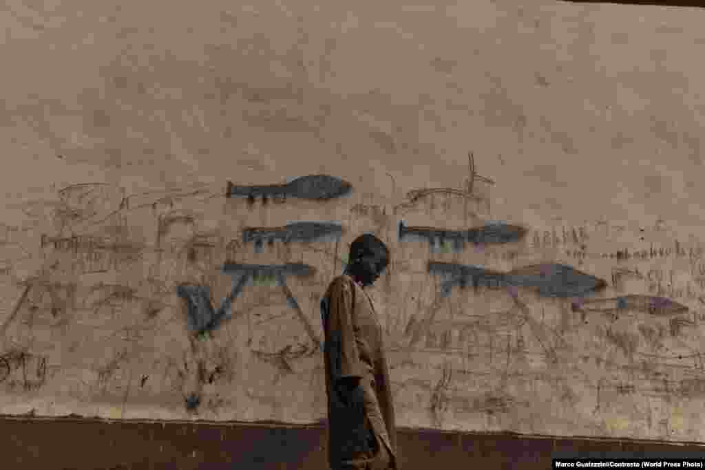 An orphaned boy walks past a wall with drawings depicting rocket-propelled grenade launchers, in Bol, Chad.  A severe humanitarian crisis has struck the Lake Chad basin due to war and the drying up of the lake, causing mass malnutrition. Environment: First Prize, Singles - Marco Gualazzini, Contrasto