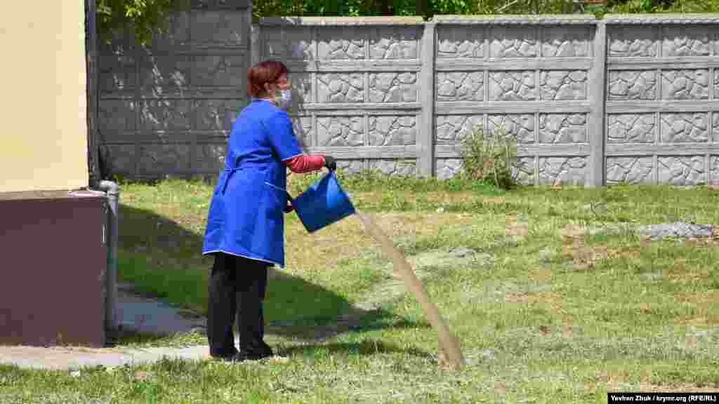 Продавщица выливает воду после уборки в сельском магазине