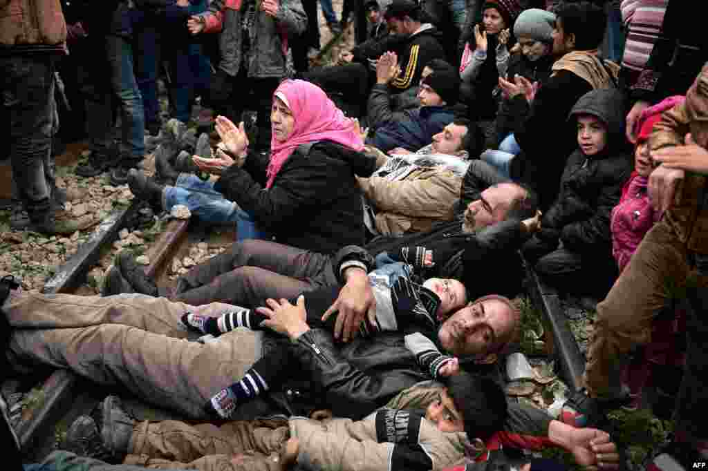 "Syrian and Iraqi refugees trapped at the Greek-Macedonian border lie on railway tracks during a protest demanding the opening of the Idomeni crossing. Greece warned the number of refugees and migrants on its soil could more than triple next month, reaching as many as 70,000, as a Balkan cap on border crossings left thousands ""trapped"" in the country. (AFP/Louisa Goulimaki)"