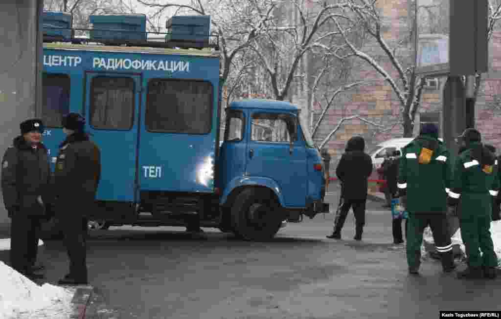 Полицейские рядом с машиной, в которой расположился центр радиофикации, стоят позади площади, где проходил митинг в честь 25-летия Декабрьских событий. Алматы, 17 декабря 2011 года.